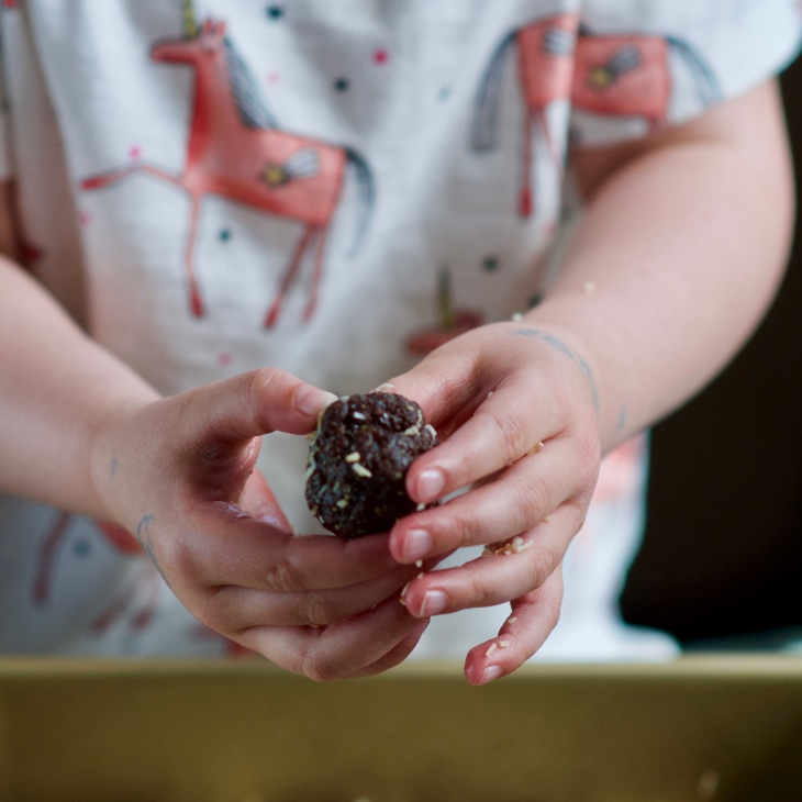 small hands holding a date almond ball